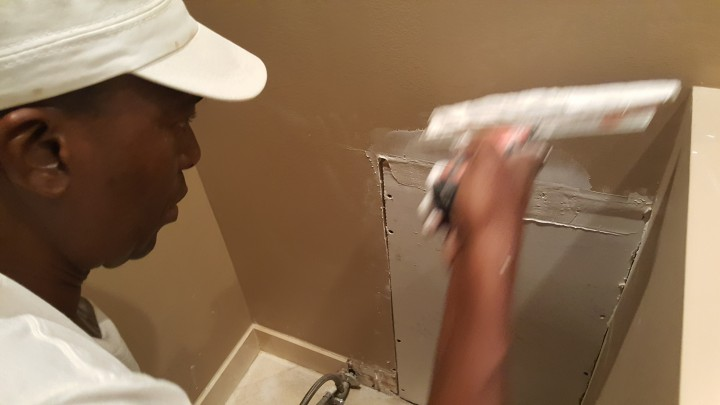 Drywall repair being performed by an experienced Watson's Painting & Waterproofing Company drywall technician.